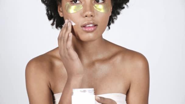vonzó afro-amerikai lány nézett konténer, szem folt véve arckrém, alkalmazása arcon, és mosolyogva, fehér
