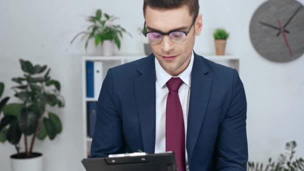 pohledný podnikatel písemně do schránky, s úsměvem a při pohledu na fotoaparát