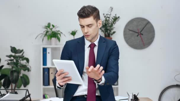 pohledný vážné obchodní muž pomocí digitálních tabletu v kanceláři