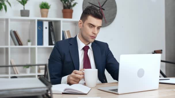 handsome businessman using laptop, looking at notebook, drinking coffee and writing in clipboard while sitting at workplace in office
