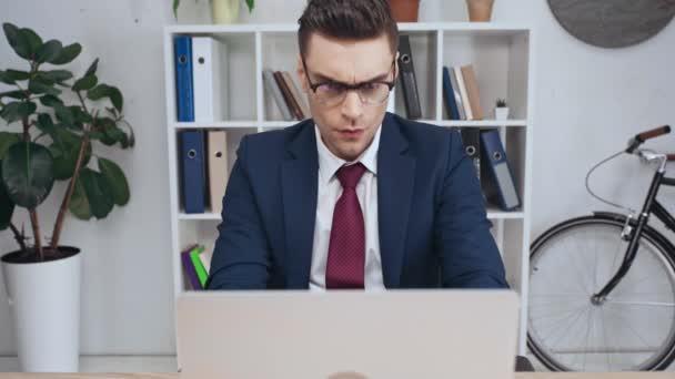 nespokojený podnikatel přenosném počítači při sezení na pracovišti v úřadu