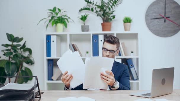 Zpomalený pohyb šťastné podnikání člověka házení dokumentů a zobrazení Ano gesto při sezení u stolu v kanceláři