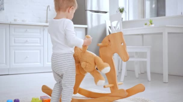 cute toddler boy holding teddy bear and playing with building blocks on rocking horse