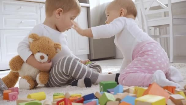 confused and smiling toddler boy sitting on carpet with teddy bear while baby sister touching his face
