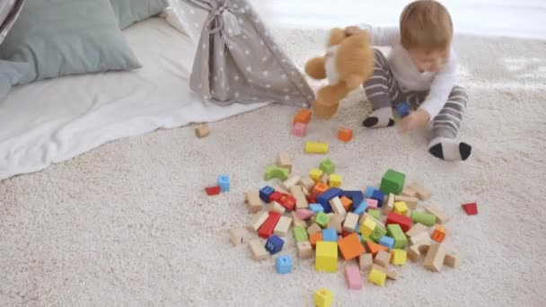 toddler boy sitting on carpet with teddy bear and baby sister and playing with wooden blocks together