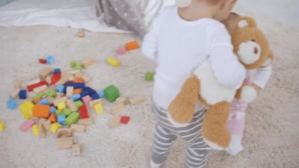 toddler boy picking up wooden blocks while baby sister sitting on carpet and playing with cubes
