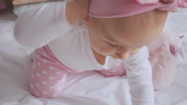 cute smiling child taking off pink headband while sitting on bed