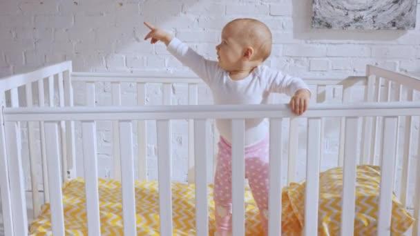 usměvavý dítě stojící v dětské postýlce a ukazování prstem kolem