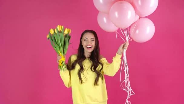 Studioaufnahme einer glücklichen jungen Frau, die rosa Luftballons in der Hand hält, gelbe Tulpen riecht und auf karminrotem Hintergrund tanzt