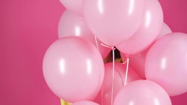 Stúdió lő, boldog fiatal nő, rózsaszín levegő léggömbök a crimson háttér mögé bújva
