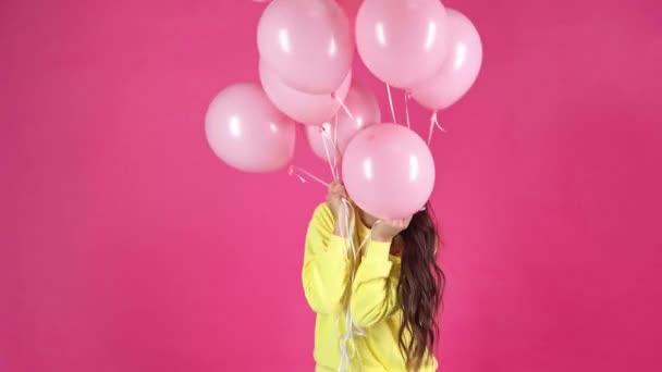 Studio střílet šťastné mladé ženy drží růžové s vrtulovým pohonem a otočila na Rudé pozadí