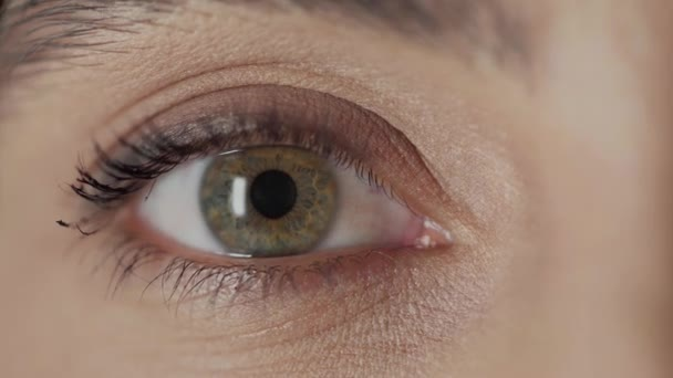 close up view of woman with green eye looking at camera