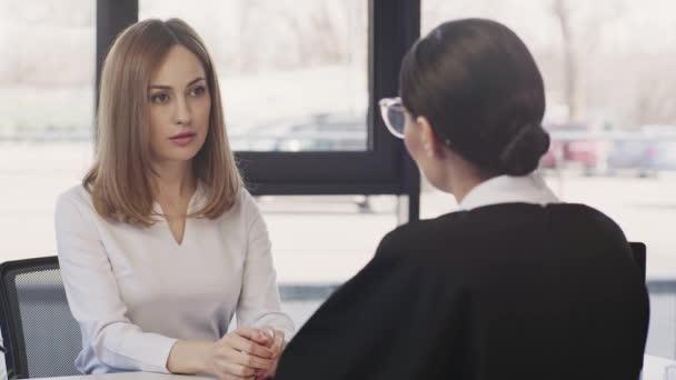 Rückansicht einer Geschäftsfrau, die mit einer aufgebrachten Frau spricht, die nickt, aufsteht und nach dem Vorstellungsgespräch geht