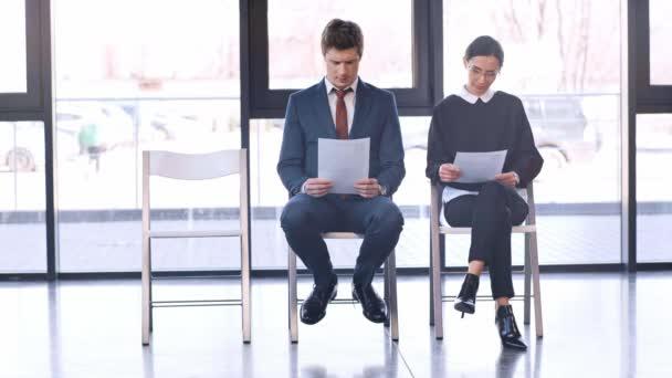 pohledný muž, který sedí na židli u ženy v brýlích a dívá se na ženu v podpatcích, kteří chodí do kanceláře