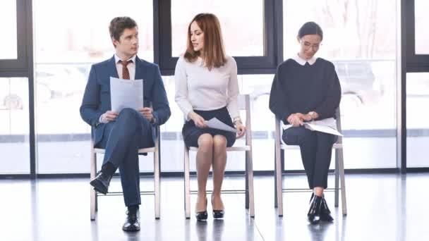 attraktive Frau, die in High Heels geht, auf einem Stuhl sitzt und vor dem Vorstellungsgespräch mit fröhlichen Menschen spricht, die Lebensläufe halten