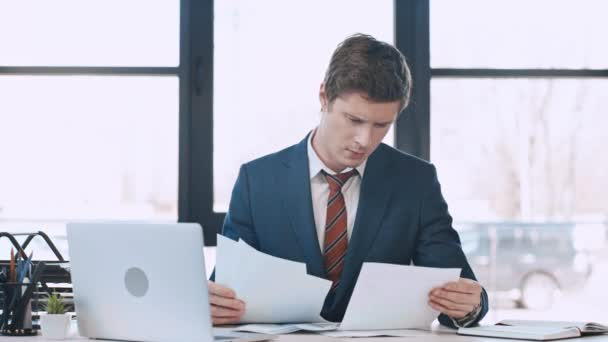 upset businessman looking at contracts while sitting near laptop and throwing papers in air in modern office