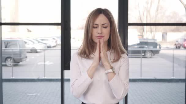 attraktive besorgte Frau mit gedrückten Daumen klatschende Hände vor Vorstellungsgespräch