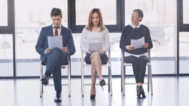 Geschäftsfrau mit Brille schaut auf Uhr, während nachdenklicher Mann den Kopf in der Nähe einer Frau berührt, die Lebenslauf betrachtet, aufsteht und geht