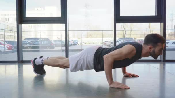 Sportsman in sneakers doing push ups in gym