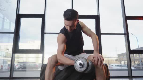 Soustředěný svalnatý sportovec v bílých šortkách s Kučerovou kadeří