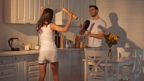 cheerful brunette woman dancing with pepper shaker near happy bearded man with frying pen and wooden spoon in kitchen