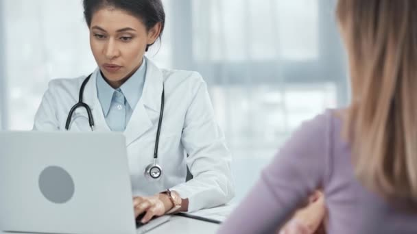 african american doctor with stethoscope talking to patient, using laptop and writing on clipboard in clinic