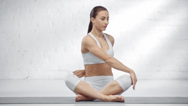 attractive young woman sitting with crossed legs showing namaste sign, practicing yoga and smiling at camera
