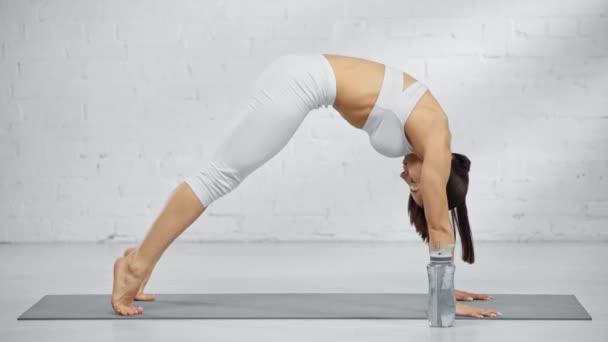 žena cvičí vlnové prkno, otírá čelo, pitnou vodu a dívá se na kameru s úsměvem