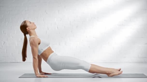 mezítláb nő gyakorló purvottanasana és Paschimottanasana a jóga mat