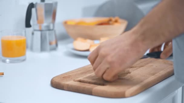 cropped view of man peeling banana and cutting it on wooden chopping board in kitchen