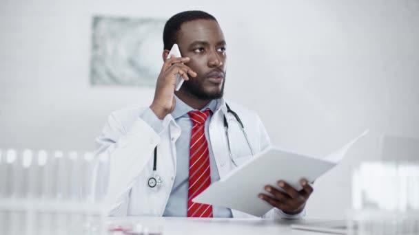 vážný africký Američan doktor, který mluví na telefonu, zatímco sedí na pracovišti a drží papírové složky