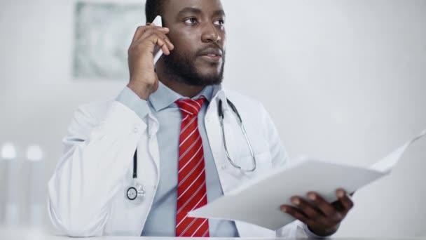vážný africký Američan doktor, který se dívá na papíry ve složce při sezení na pracovišti a mluvení na smartphone