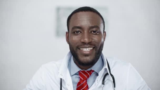 gutaussehender, fröhlicher afrikanisch-amerikanischer Arzt, der in die Kamera lächelt