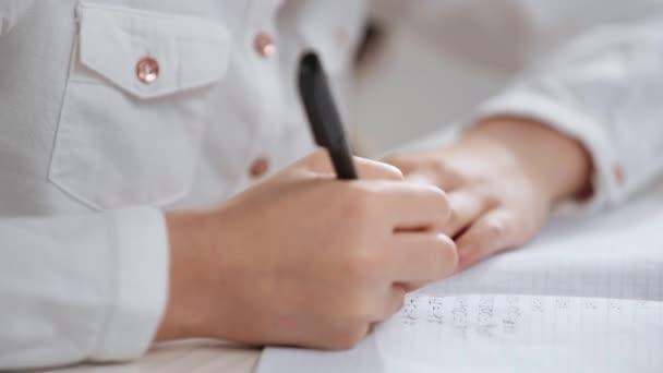 részleges tekintettel iskolás fehér inget csinál házi feladatot, és írásban a másolás könyv