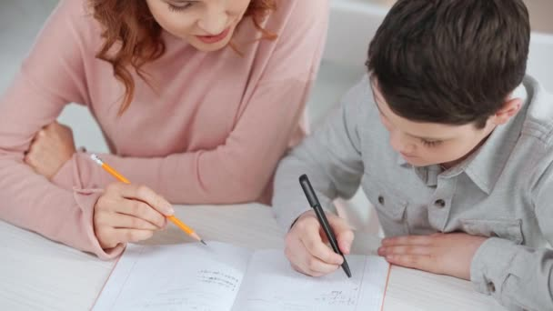 mother holding pencil and helping son with homework while he writing on copy book at desk