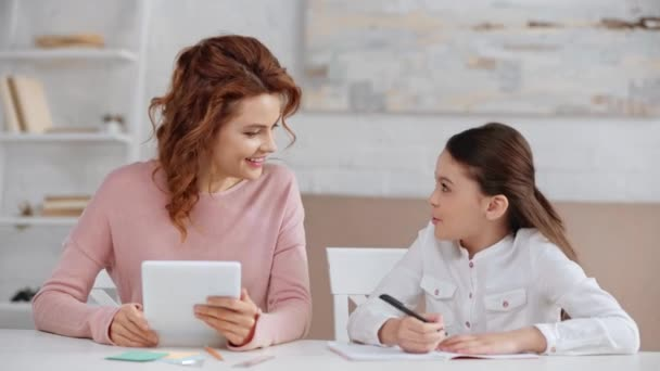 beautiful smiling mother using digital tablet at desk while daughter doing homework