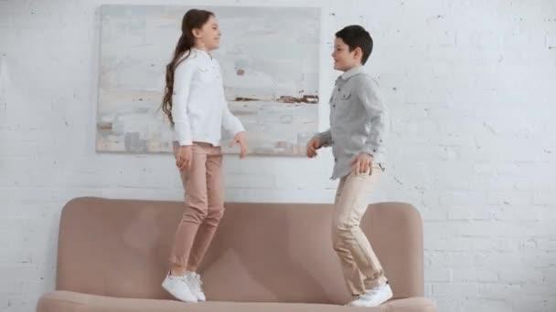volle Länge Ansicht von zwei glücklich lächelnden preteen Kinder springen und tanzen auf dem Sofa im Wohnzimmer