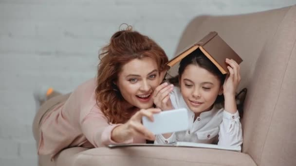 cheerful preteen child putting book on head, taking selfie with mother and smiling while lying on sofa at home