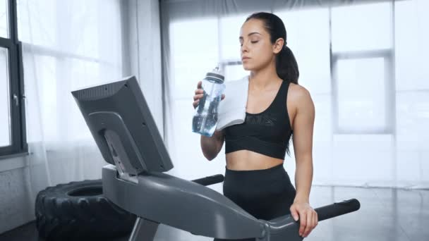 schöne Sportlerin auf dem Laufband, die Wasser trinkt, in die Kamera schaut und im Fitnessstudio lächelt