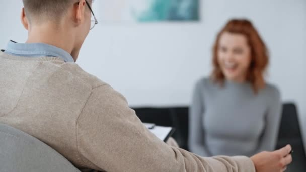 selective focus of psychologist smiling with patient