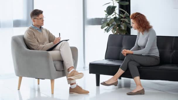 sad patient sitting and talking with psychologist