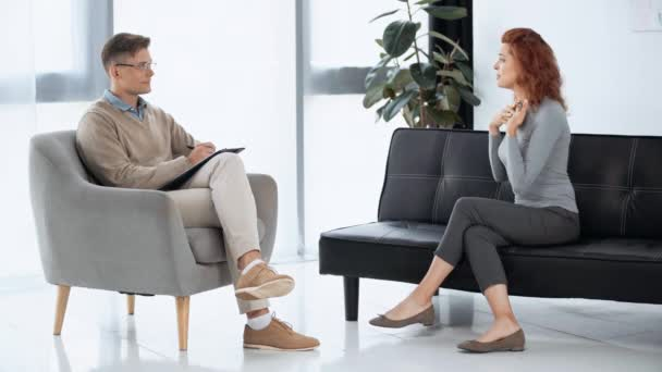 smiling patient talking with psychologist in glasses