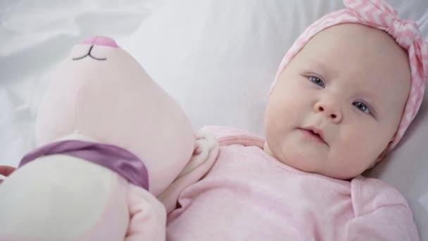 aranyos csecsemő feküdt ágyon puha játék