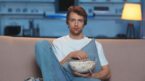 smutný člověk jíst popkorn při sledování televize v obývacím pokoji