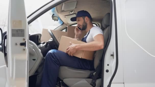 tense delivery man talking ton smartphone with parcels in car