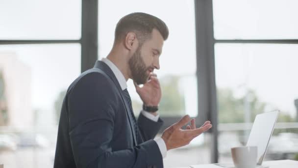 obchodník hovoří o smartphone a používání laptopu v kanceláři