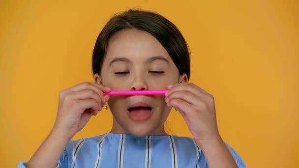 legrační dítě, které dělá falešný knírek tužkou izolovanou na žlutém