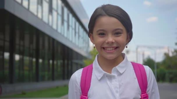boldog iskolás tisztelegve és a gyaloglás az iskolaudvaron