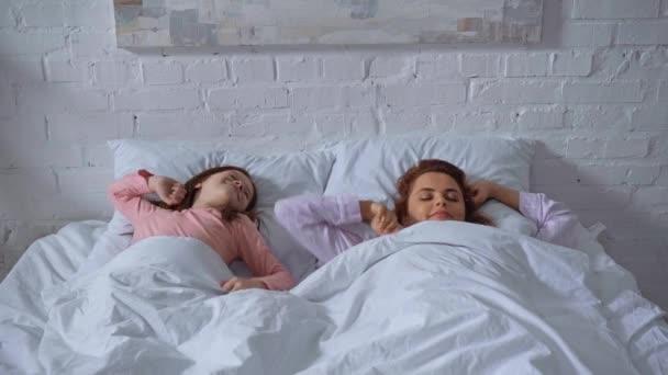 šťastná matka a dcera se probudili a drželi se za ruce v posteli