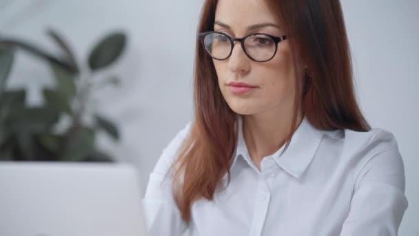 usměvavá žena v brýlích na kameru